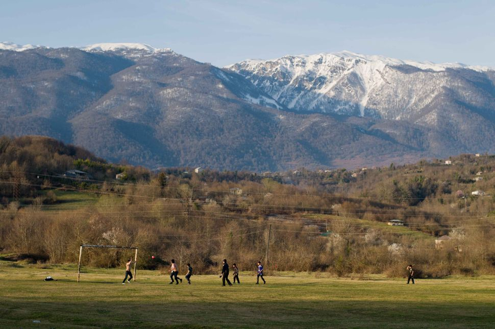 Football match with snowy mountain background