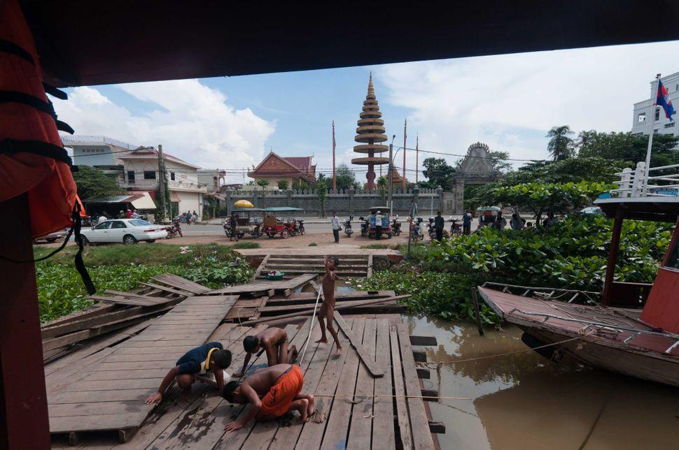 Boys fishing through the planks, Phnom Penh