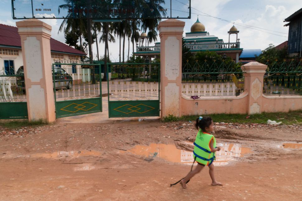 Girl in a safety vest walking a riverside street in front of a mosque, Phnom Penh