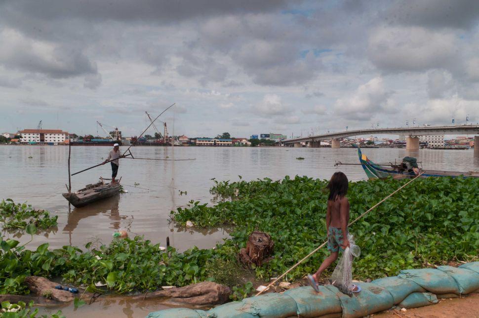 Girl walking on the sandbag barrier, Phnom Penh