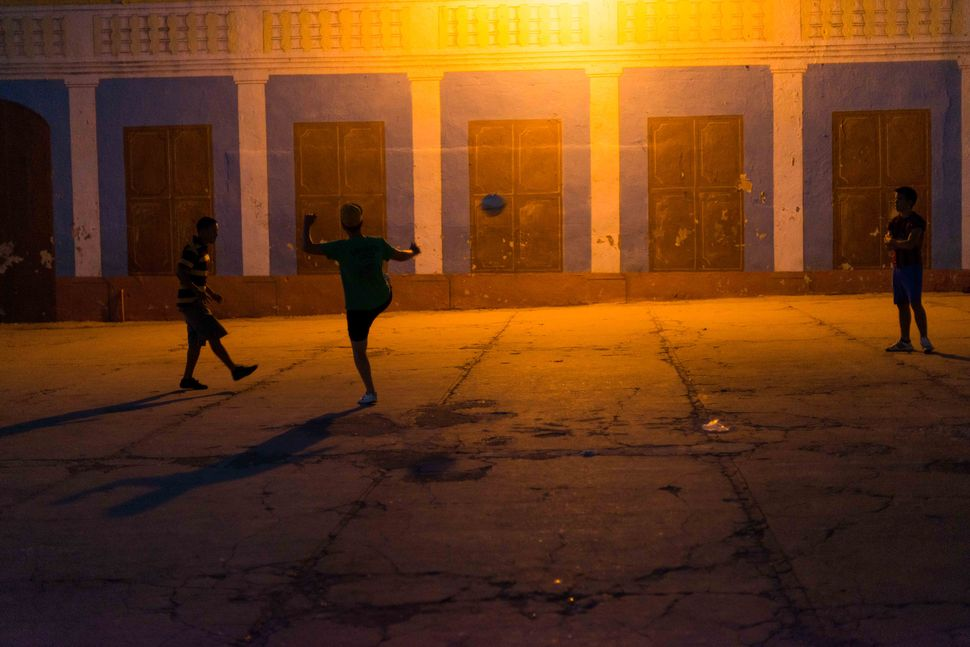 Kids playing football under a bulb light, Trinidad, 2