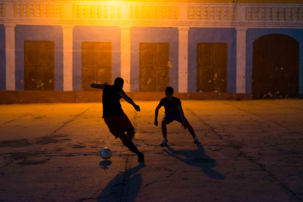 Kids playing football under a bulb light, Trinidad