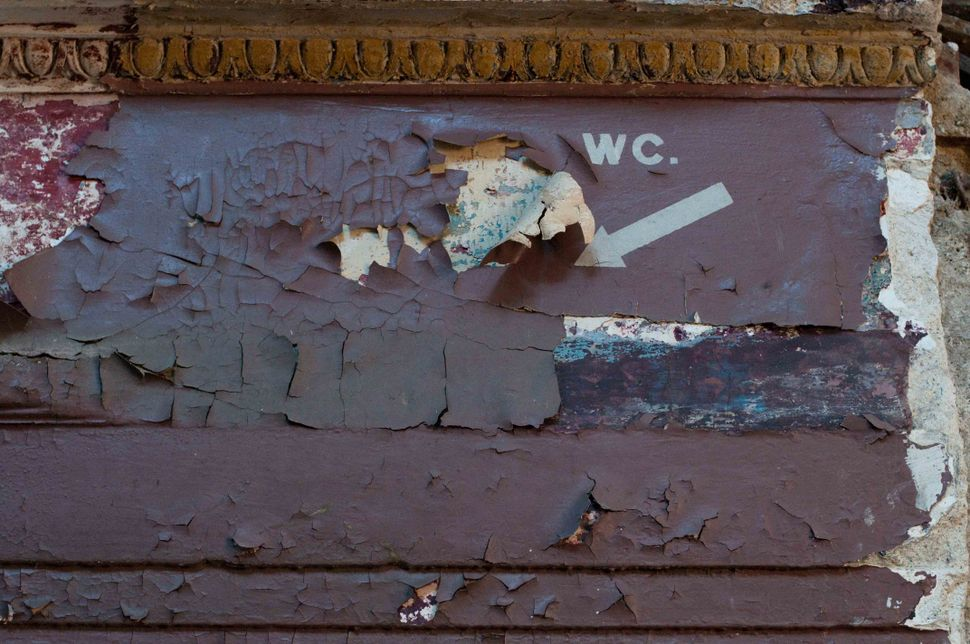 WC sign on peeling wall