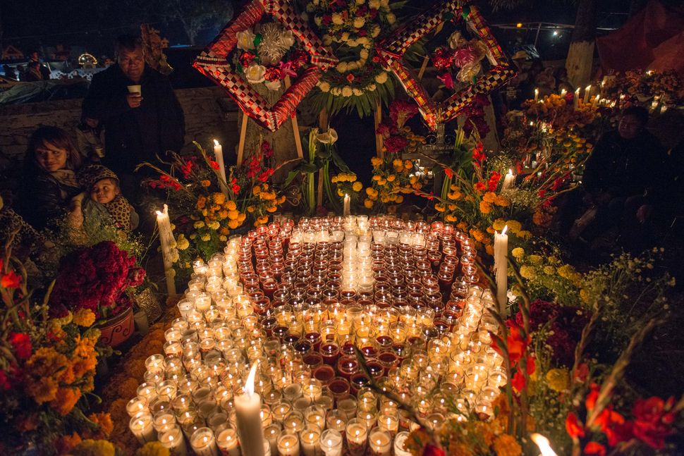 Family around grave adorned with candles, Tzintzuntzan