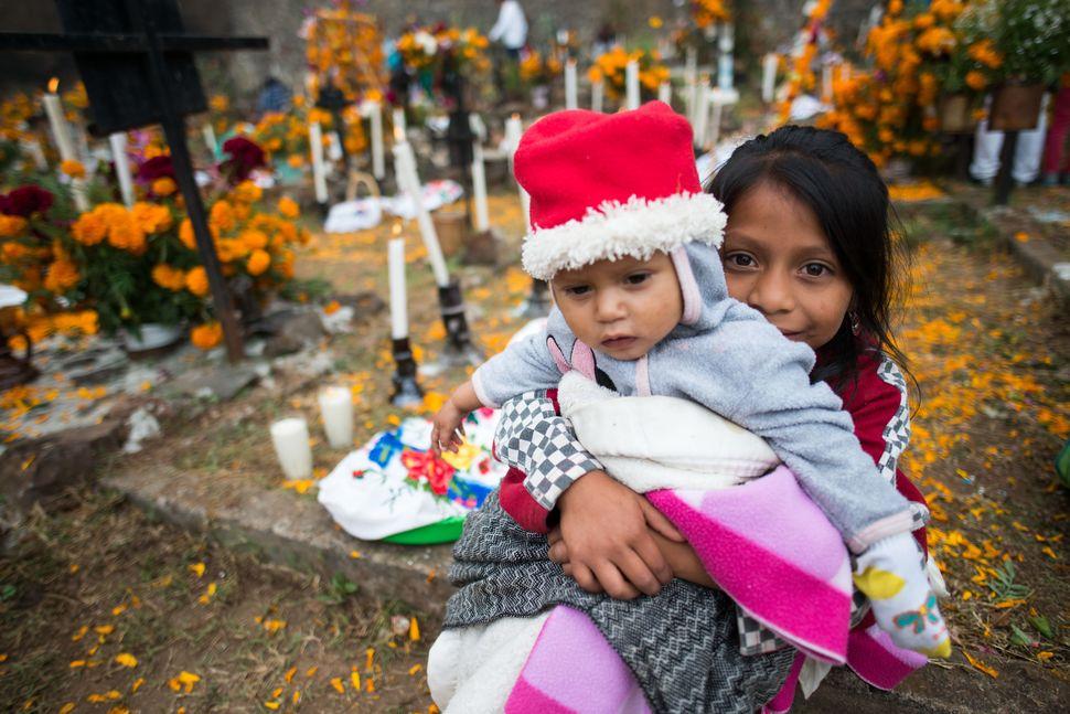 Girl holding her baby sibling, Janitzio