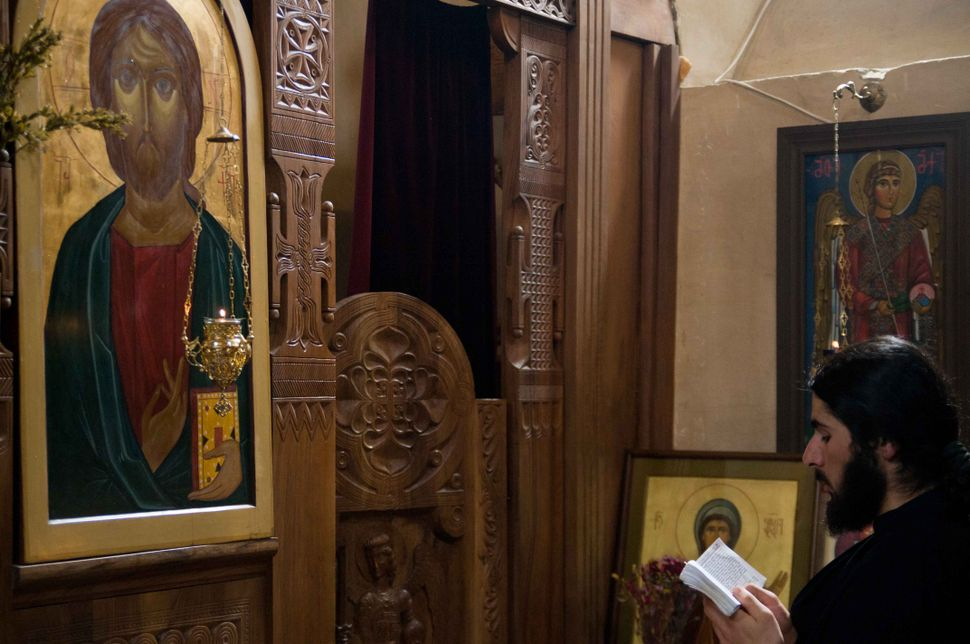 Deacon reading in the church, Kazbegi