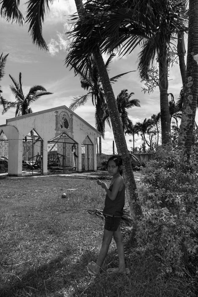 Little girl in front of devastated church