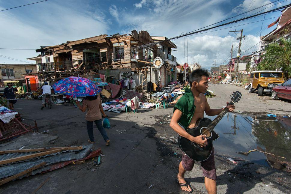 Guitarist strumming his guitar in front of pile of debris