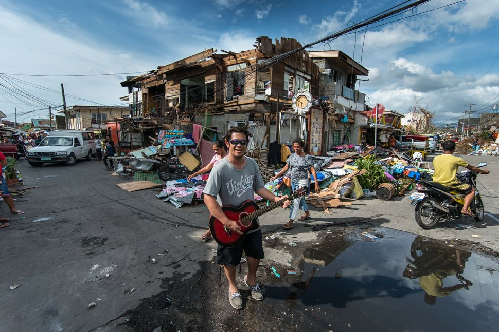 """Musician playing Lynyrd Skynyrd´s """"Tuesday´s Gone"""" in front of debris"""
