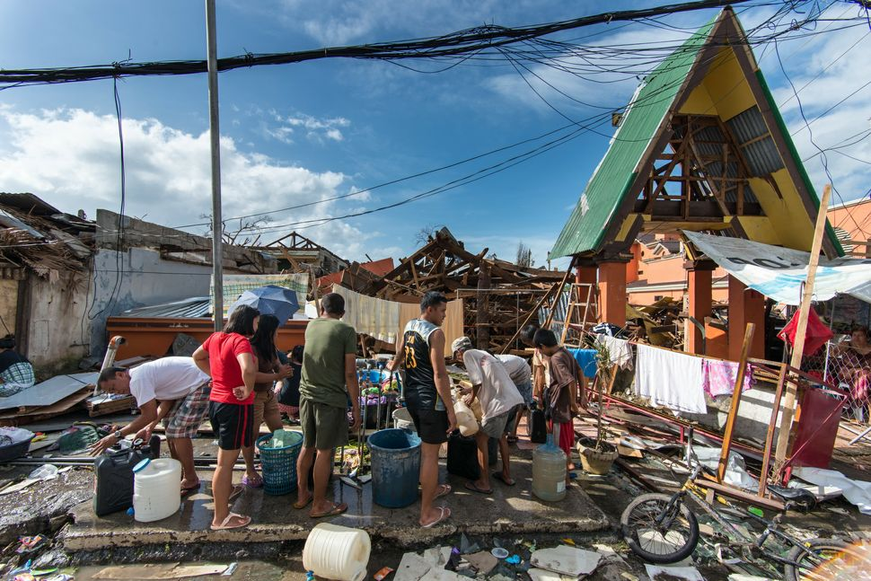 Queueing for water in front of damaged houses