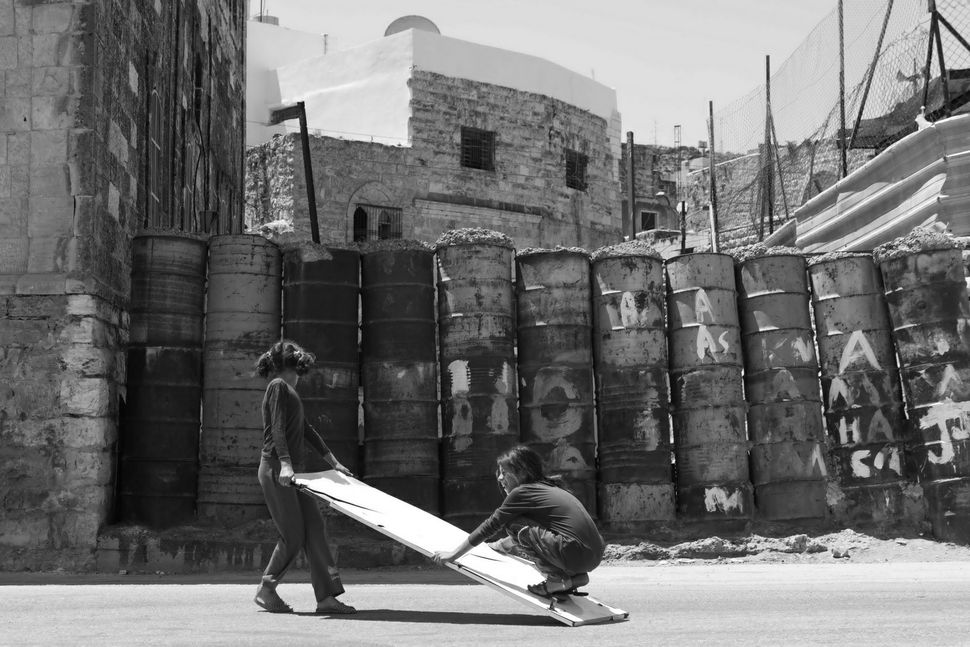Palestinian girls carrying a plank (and playing)