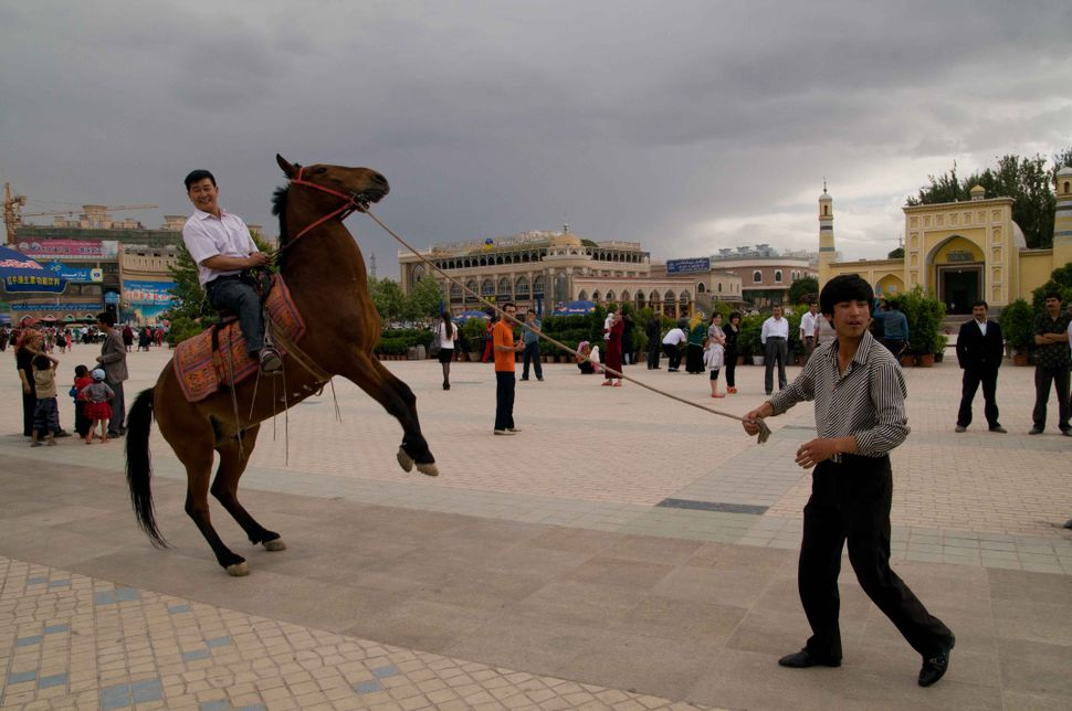 Horse riding in front of id Kah Mosque, Kashgar, 2