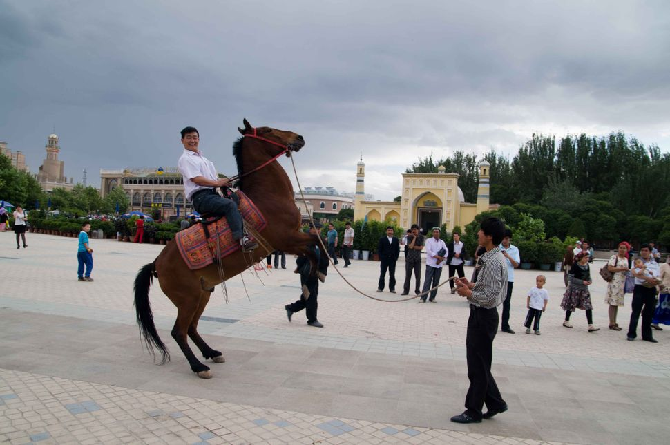 Horse riding in front of id Kah Mosque, Kashgar