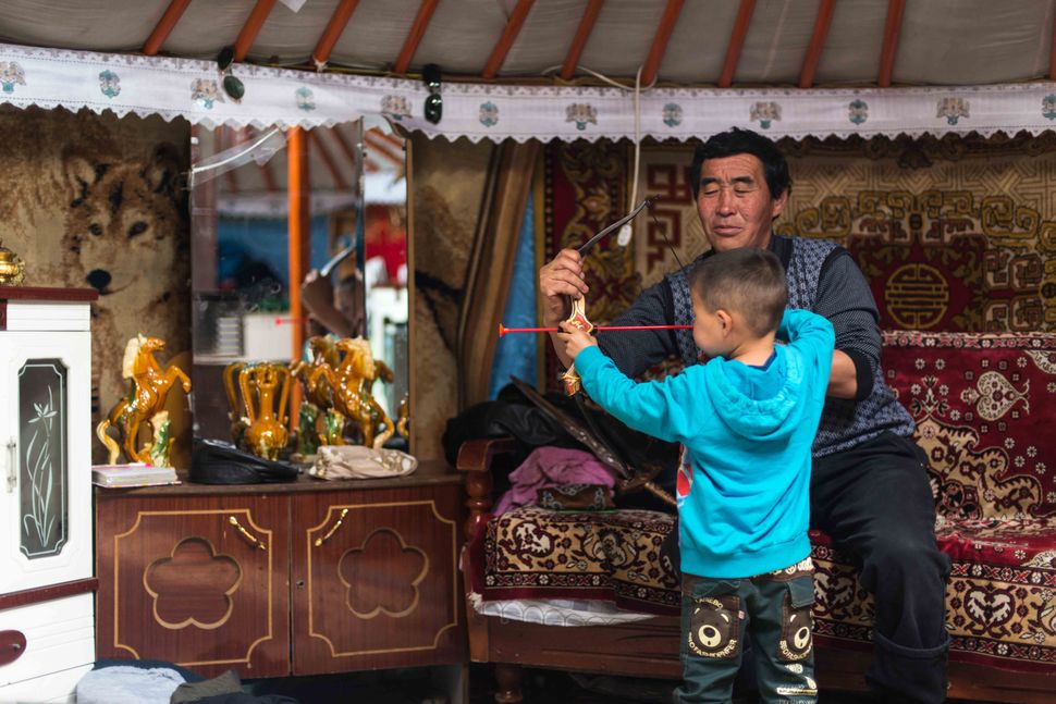 Ulan Bator - Ger district, father teaching son to shoot with bow and arrow