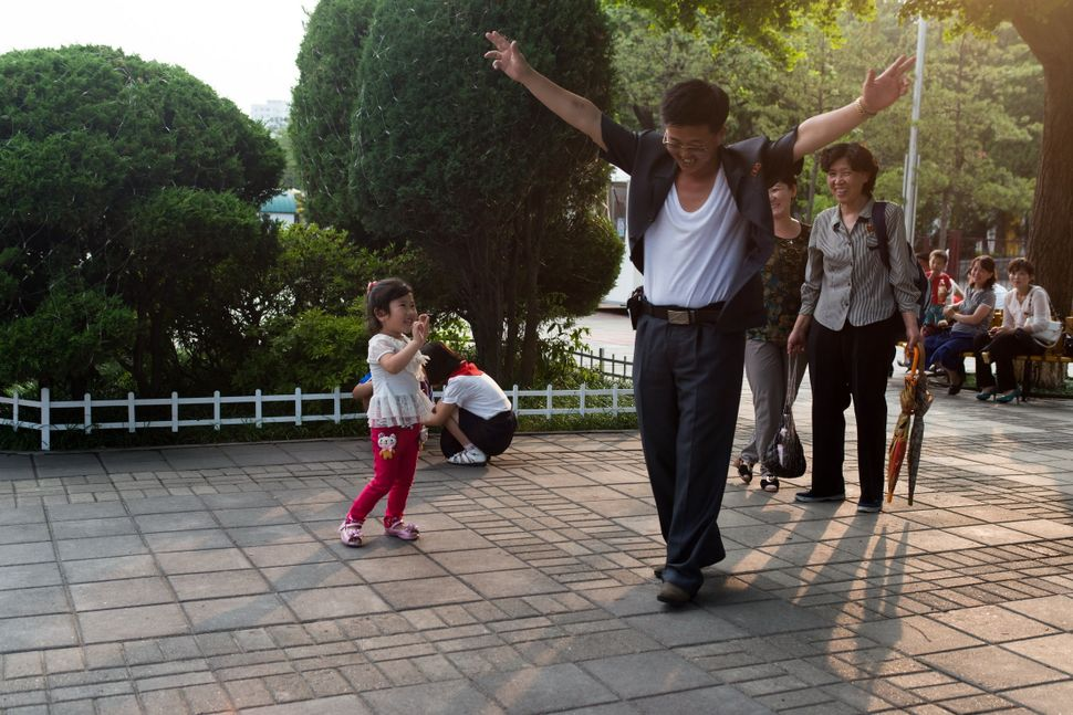 Joy - Father dancing in front of daughter in the amusement park in Pyongyang