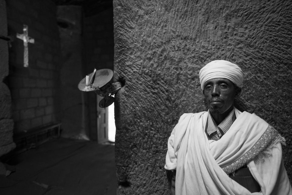Monk with lamp in St. Merkorios church, Lalibela