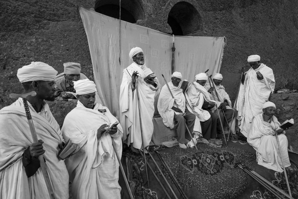 Priests praying in the court of Bete Maryam church, Lalibela
